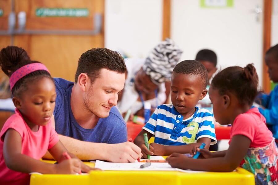 Maestro sentándose con niños pequeños en un aula
