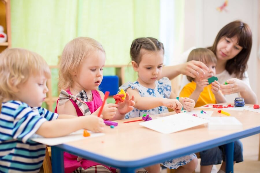 Children and a woman playing with play dough at a table