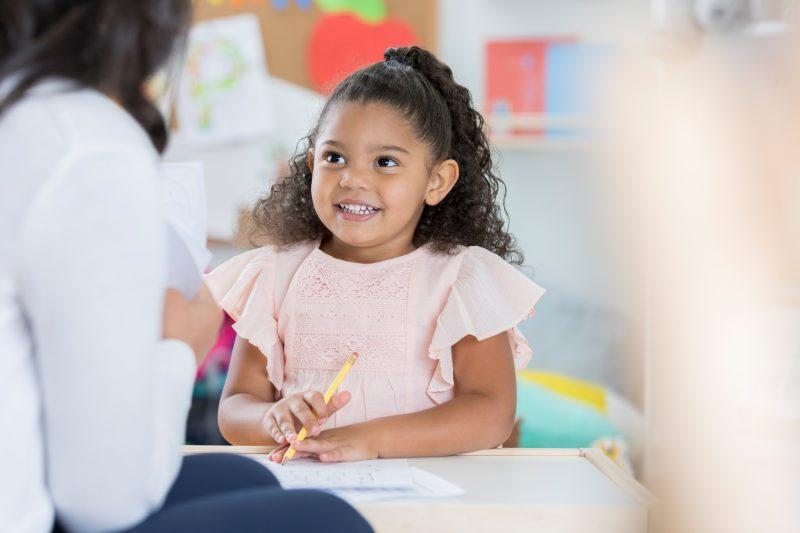 Niña de edad preescolar sonriendo y mirando a su maestra